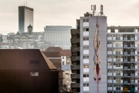 A mural of a gutted body hanging upside down with blood seeping out, is painted on an apartment building in Brussels on Thursday, Jan. 26, 2017. Depicting details from Caravaggio and Dutch Master paintings, an anonymous street artist is the talk of the town and again asks that age-old question about art: how far can it go before it outrages just too much. (AP Photo/Geert Vanden Wijngaert)